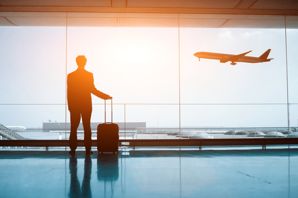 Silhouette of person in the airport, with a suitcase, watching a plane take off