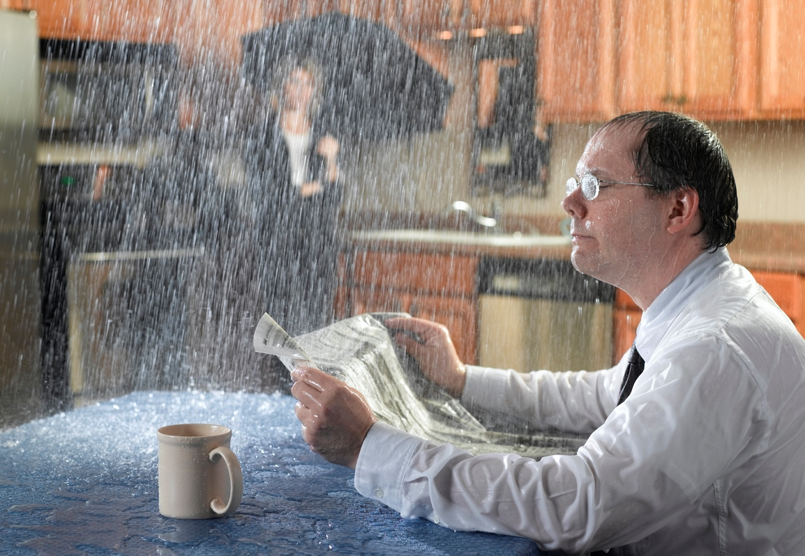 Businessman sitting in kitchen reading morning paper, ignoring rain pouring through the ceiling