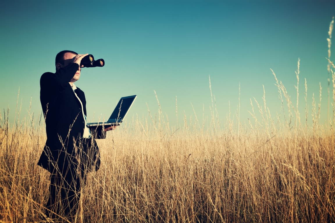 Businessman standing in paddock holding a laptop and looking through binoculars