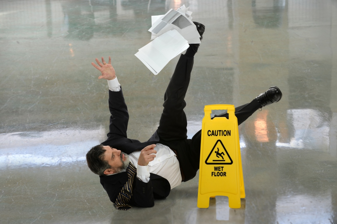 Businessman slipping over next to wet floor sign & dropping papers
