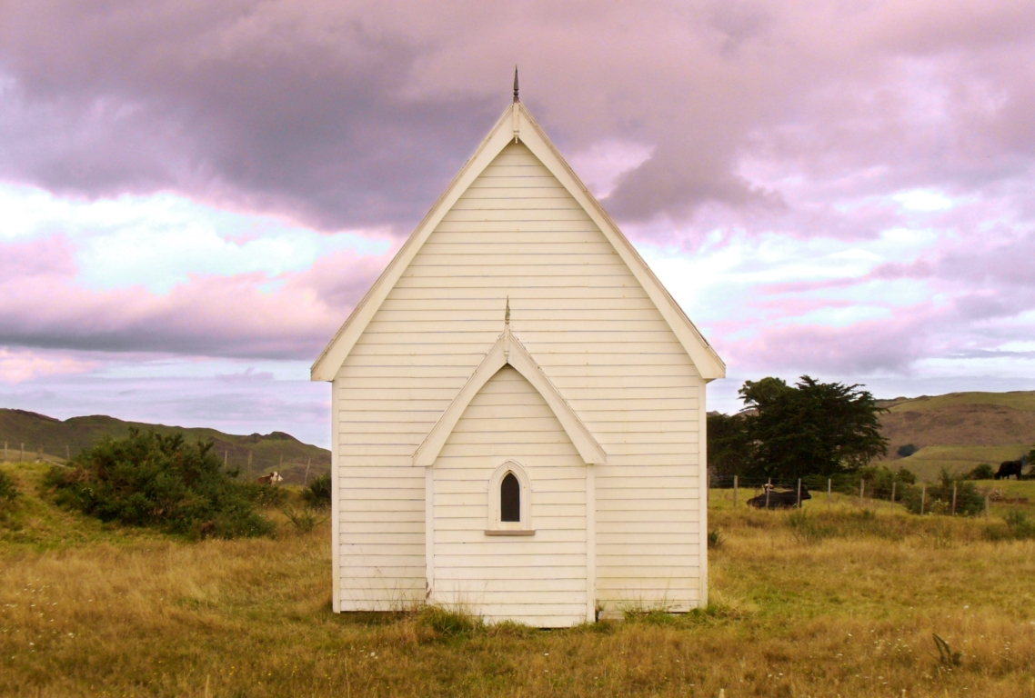 Small white church in a country paddock with cows