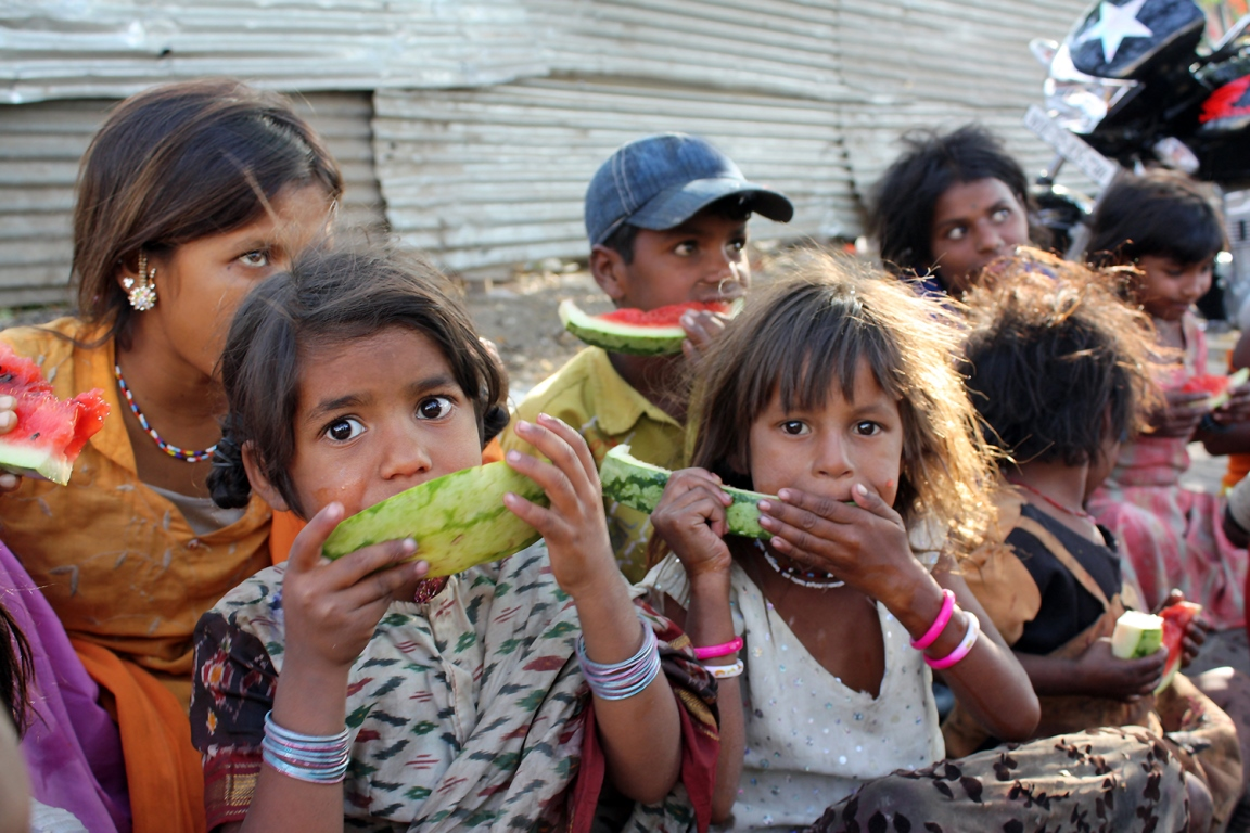 Children and parents sharing watermelon while sitting on footpath